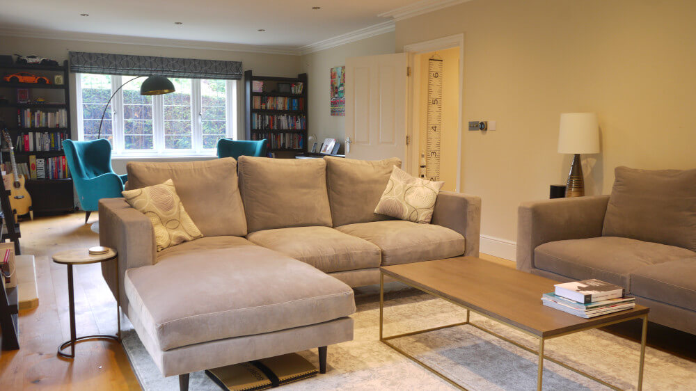 contemporary living room weybridge with l-shaped sofa and reading corner behind with teal chairs